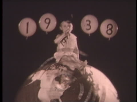 stockvideo's en b-roll-footage met b/w 1938 boy sitting on globe as new year / dissolves into father time + clock - 1938