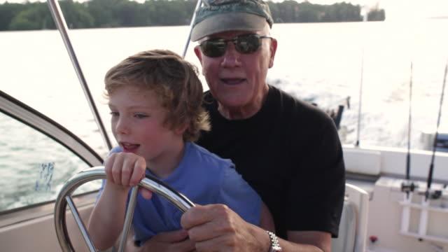 vídeos de stock, filmes e b-roll de cu boy sitting on his grandfather's lap and driving boat in lake / wolfebro, nh, usa      - artigo de vestuário para cabeça