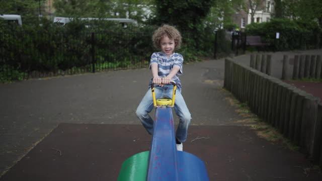 vídeos y material grabado en eventos de stock de ws pov boy (4-5) sitting on seesaw moving up and moving down, laughing / london, united kingdom  - balancín