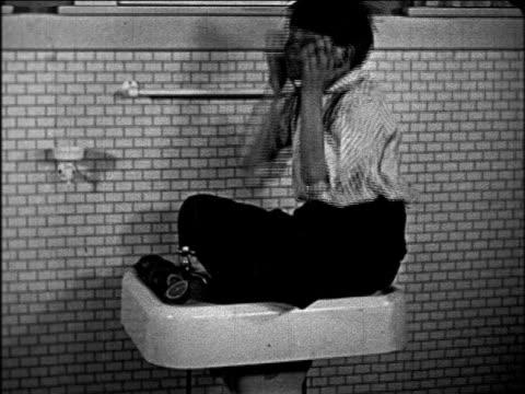 B/W 1927 boy sitting on sink scrubbing face with lemon / educational