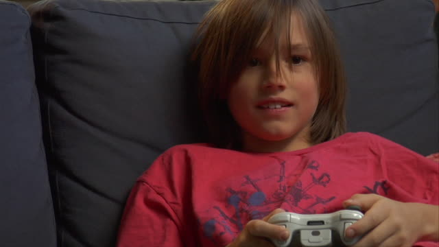 CU, Boy (8-9) sitting on sofa, playing video game