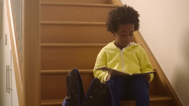 vidéos et rushes de boy sitting on stairs reading a book - niveau primaire