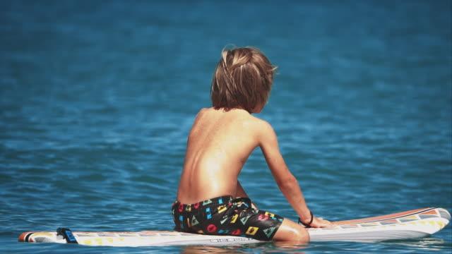 stockvideo's en b-roll-footage met jongen zittend op surfplank zweven in de oceaan - alleen jongens