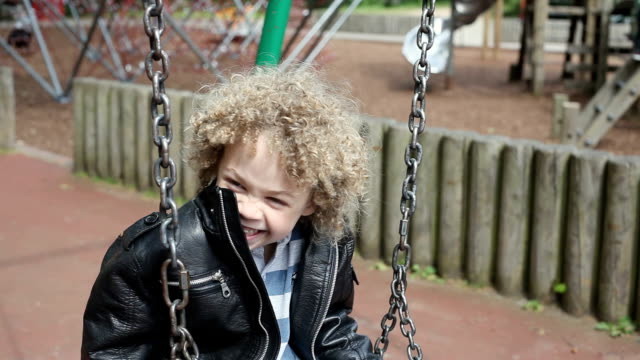 cu boy (4-5) sitting on swing and laughing / london, united kingdom - leather jacket stock videos and b-roll footage