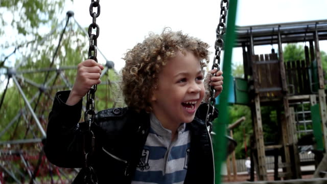 cu pov boy (4-5) sitting on swing, swinging and laughing / london, united kingdom - leather jacket stock videos and b-roll footage