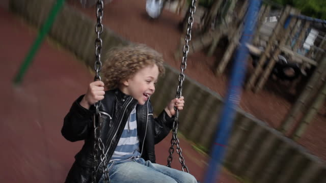 ms pov boy (4-5) sitting on swing, swinging and laughing / london, united kingdom - leather jacket stock videos and b-roll footage