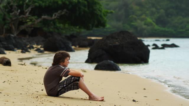 boy sitting on the beach - endast en tonårspojke bildbanksvideor och videomaterial från bakom kulisserna