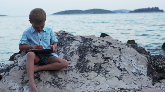 Boy sitting on the rocky shore.