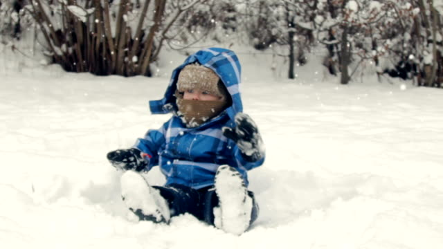 boy sitting on the snow - winter coat stock videos & royalty-free footage
