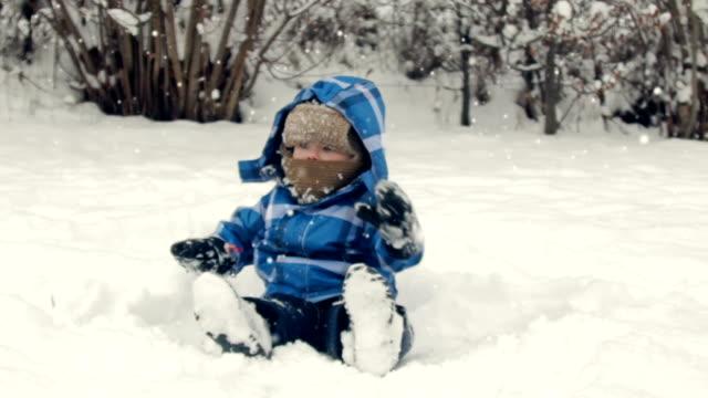 ragazzo seduto sulla neve - cappotto invernale video stock e b–roll