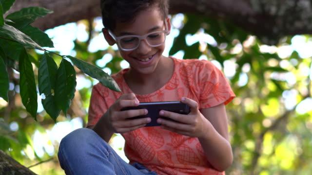 vídeos de stock, filmes e b-roll de menino que senta-se na árvore usando um telefone esperto - parque natural