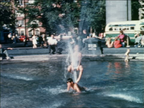 vídeos de stock e filmes b-roll de 1960 boy sitting on top of fountain with other boy swimming / washington square park, nyc - 1960