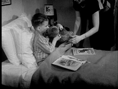 stockvideo's en b-roll-footage met 1955 film montage ms boy sitting  up in bed and reading as mother brings him teddy bear/ cu boy hugging bear/ audio - prentenboek