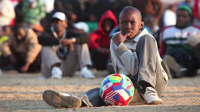 ws boy sitting with people in background, soweto, gauteng, south africa, audio  - soweto stock videos and b-roll footage
