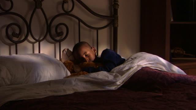 boy sleeping in bed with teddy bear - andere clips dieser aufnahmen anzeigen 1282 stock-videos und b-roll-filmmaterial