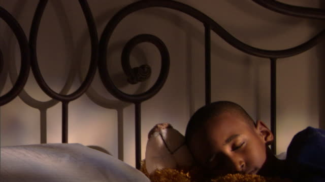 Boy sleeping in bed with teddy bear