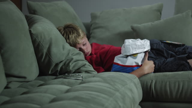 ms zi boy (12-13) sleeping with chips bag on sofa / orem, utah, usa - napping stock-videos und b-roll-filmmaterial