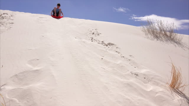 boy slides down sand dune at white sands national monument in new mexico - männlicher teenager allein stock-videos und b-roll-filmmaterial