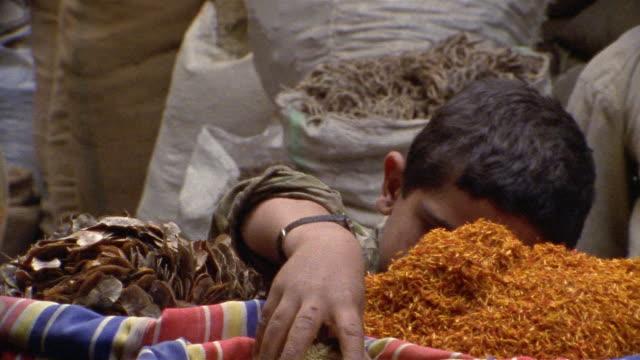 cu, boy (8-9) smelling herbs on street market, cairo, egypt - egypt stock videos & royalty-free footage