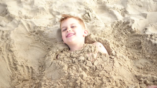 vídeos de stock e filmes b-roll de boy smiles while being buried - enterrado