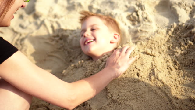 Boy smiles while being buried