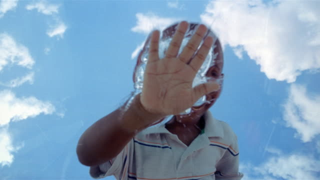 la cu boy smiling and running hand across surface of water - scoperta video stock e b–roll