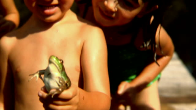cu td boy smiling as his friends surround him to touch frog he's holding/ tu boys and girls looking at frog/ bovina, new york  - teich stock-videos und b-roll-filmmaterial