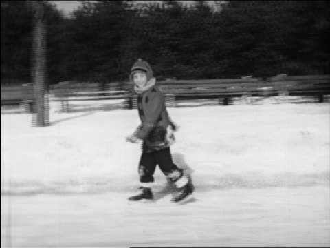 b/w 1948 boy smiling at camera + ice skating on pond / instructional - eislaufen stock-videos und b-roll-filmmaterial
