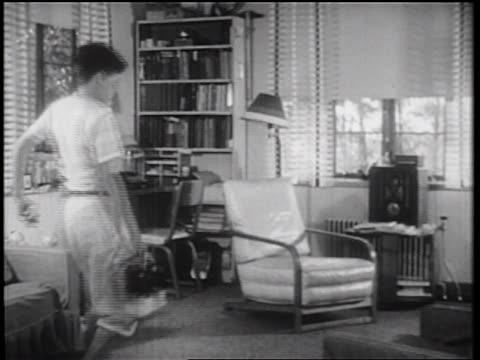 b/w 1939 boy sneaking thru living room + looking in lunch bag / documentary - tiptoe stock videos & royalty-free footage