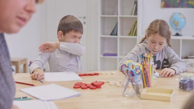 vídeos y material grabado en eventos de stock de el niño estornudaba en la mesa en la escuela - estornudar