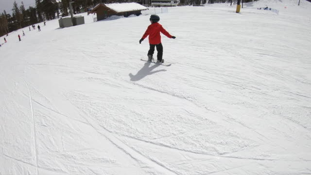 a boy snowboarder snowboarding at a ski resort. - slow motion - snowboard video stock e b–roll
