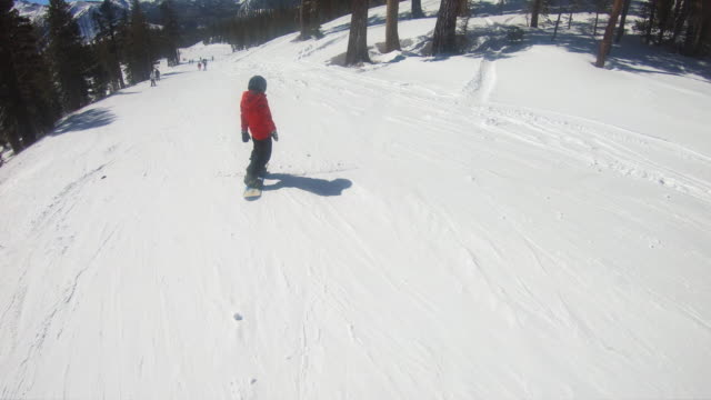 a boy snowboarder snowboarding at a ski resort. - goodsportvideo stock videos and b-roll footage