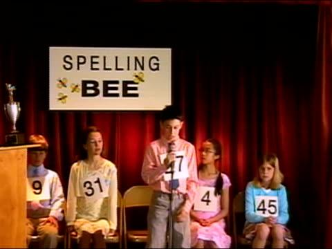 Boy spelling word on stage in spelling bee / sitting down in frustration / Los Angeles, California
