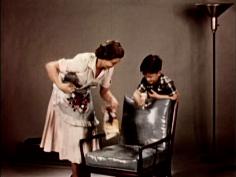 1956 MONTAGE Boy spilling ice cream onto leather chair. His mom walks over and sponges stain off of seat / USA