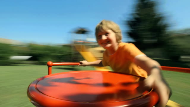 hd: boy spinning on playground merry-go-round - roundabout stock videos and b-roll footage