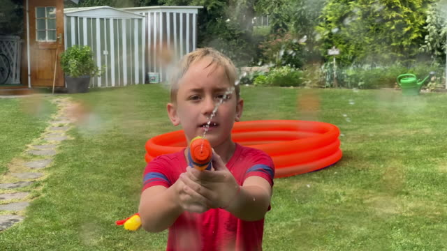 boy splashing water with water pistol to camera - water pistol stock videos & royalty-free footage