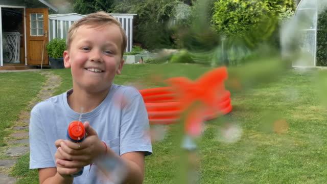 boy splashing water with water pistol to viewer - water pistol stock videos & royalty-free footage