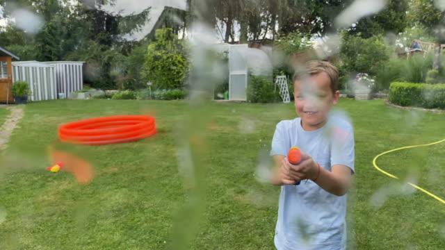 boy splashing water with water pistol - water pistol stock videos & royalty-free footage