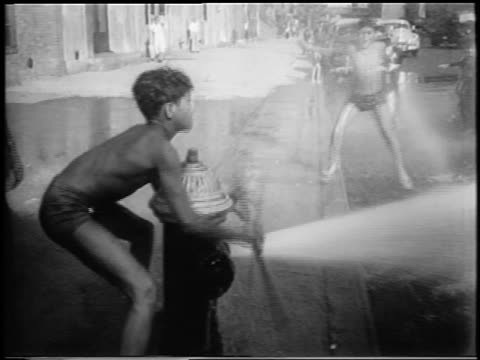 pan boy spraying fire hydrant on boys in city street / newsreel - fire hydrant stock videos & royalty-free footage