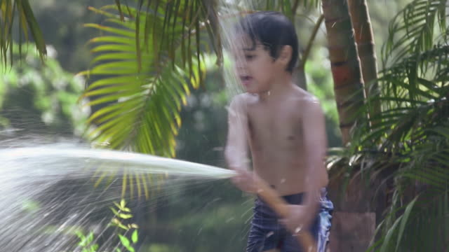 boy spraying water at park, delhi, india - only boys stock videos and b-roll footage
