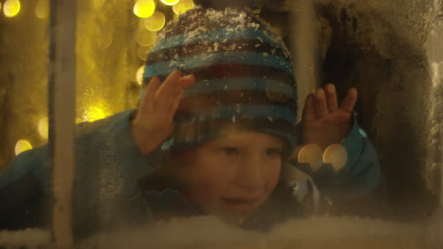 Boy spying on Santa Claus behind snowy window