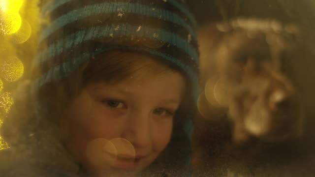 stockvideo's en b-roll-footage met boy spying on santa claus behind snowy window - open haard