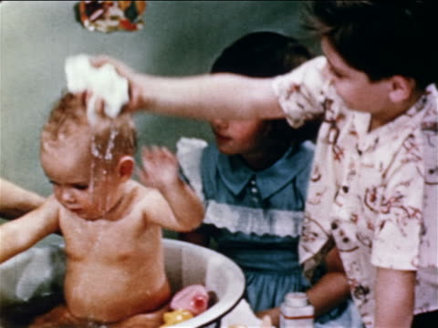 vidéos et rushes de 1950 boy squeezing water from washcloth over baby's head in washbasin / girl watching - brother