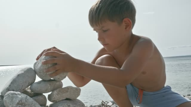boy stacking up white round rocks on the sunny beach - shirtless stock videos & royalty-free footage