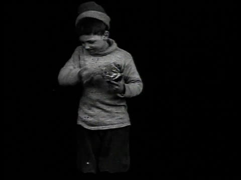 1916 ws boy standing and eating an orange, then wiping his mouth - 1916年点の映像素材/bロール