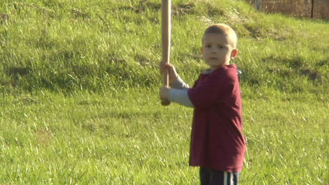 sm ms boy standing in grass and holding baseball bat/ bat slipping from boy's hands and hitting him in the face/ boy rubbing face and smiling/ chelsea, michigan - missöde bildbanksvideor och videomaterial från bakom kulisserna