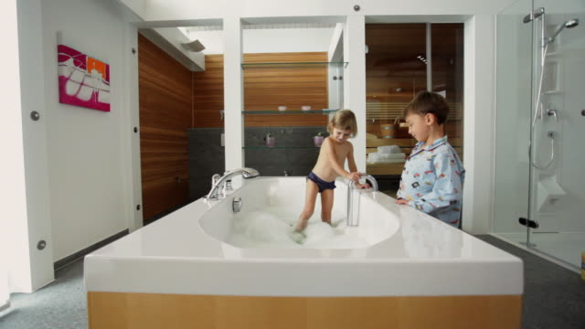 WS Boy (4-5) standing next to bathtub in pyjamas, Girl (2-3) standing in water playing with foam