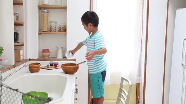 A boy standing on a chair enjoys cooking at the kitchen