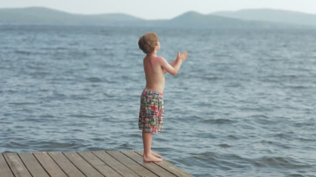 WS Boy standing on dock and jump in to lake / WOLFEBRO, NH, USA