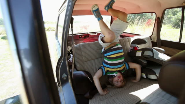 Boy standing on his head on car seat